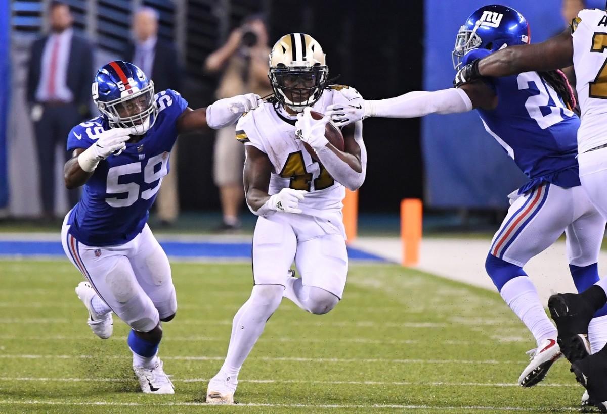 New Orleans Saints running back Alvin Kamara (41) carries between Giants linebacker Lorenzo Carter (59) and cornerback Janoris Jenkins (20). Mandatory Credit: Robert Deutsch-USA TODAY