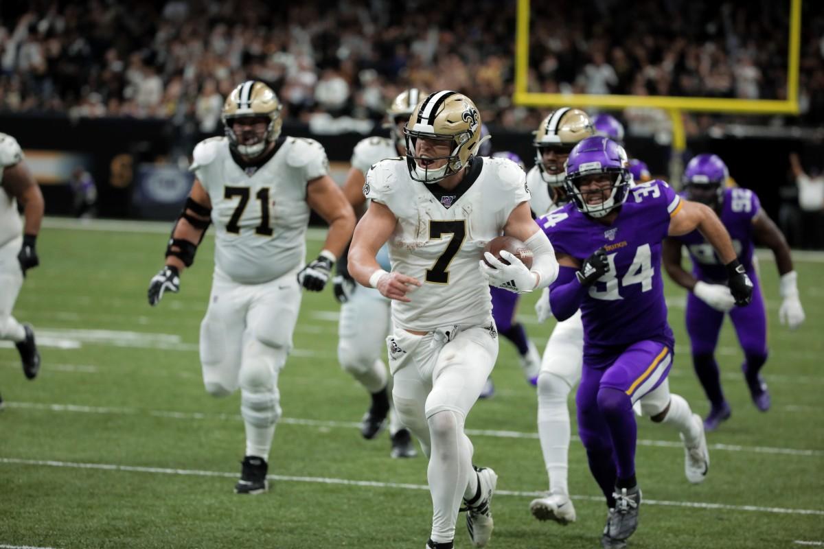New Orleans Saints player Taysom Hill (7) runs past Minnesota safety Andrew Sendejo (34). Mandatory Credit: Derick Hingle-USA TODAY Sports
