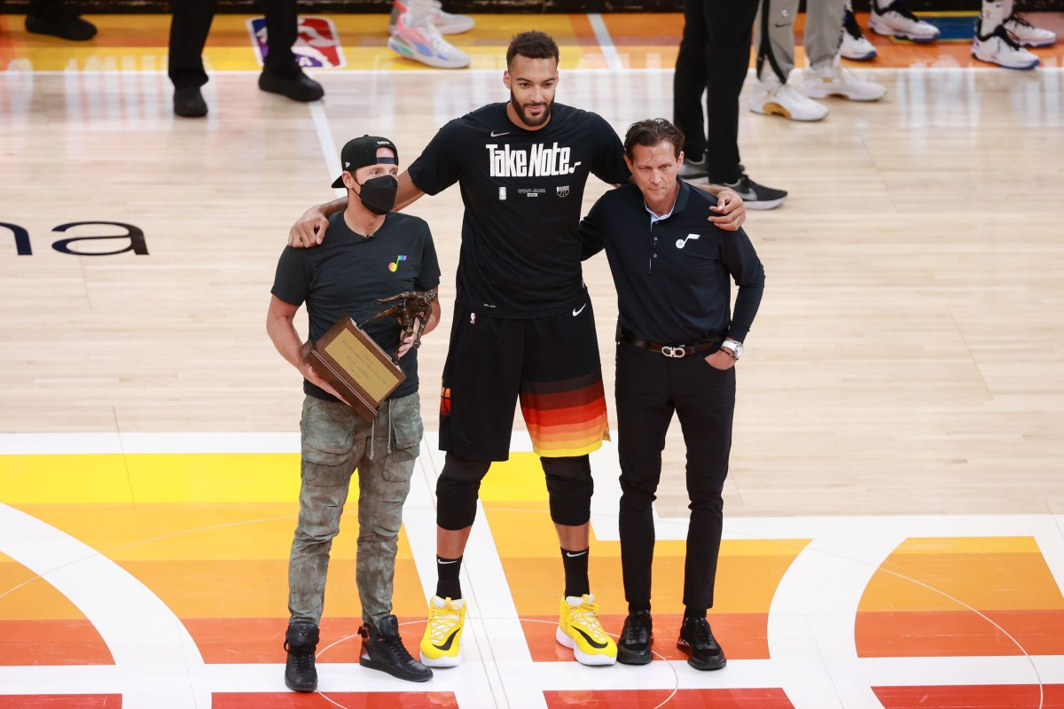 Rudy Gobert (center) is awarded the Defensive Player of the Year Award by Jazz Owner Ryan Smith (left) and Head Coach Quin Snyder (right)
