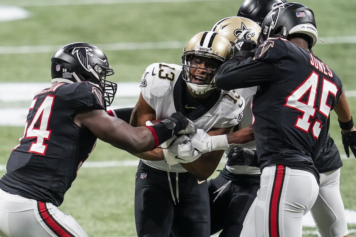 Falcons linebackers Foyesade Oluokun (54) and Deion Jones (45) try to pry the ball away from New Orleans receiver Michael Thomas (13). Mandatory Credit: Dale Zanine-USA TODAY