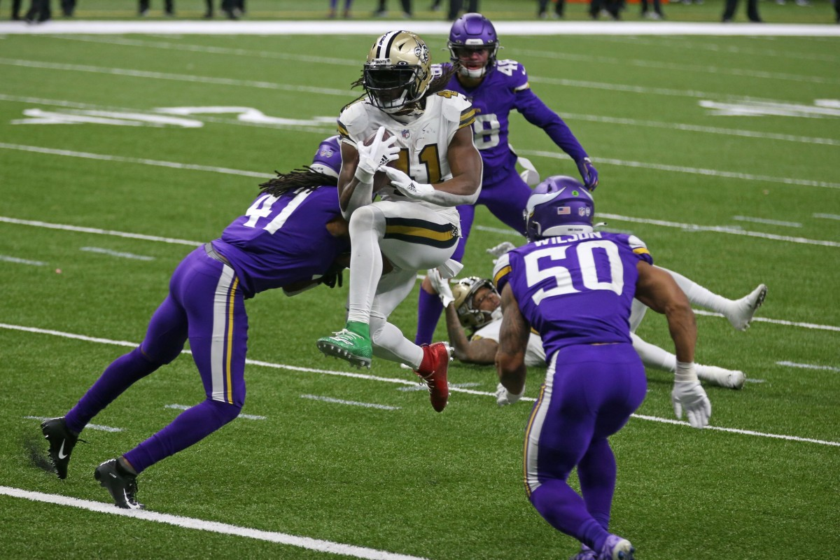 New Orleans Saints running back Alvin Kamara (41) jumps into the end zone between Minnesota Vikings Anthony Harris (41) and Eric Wilson (50). Mandatory Credit: Chuck Cook-USA TODAY Sports