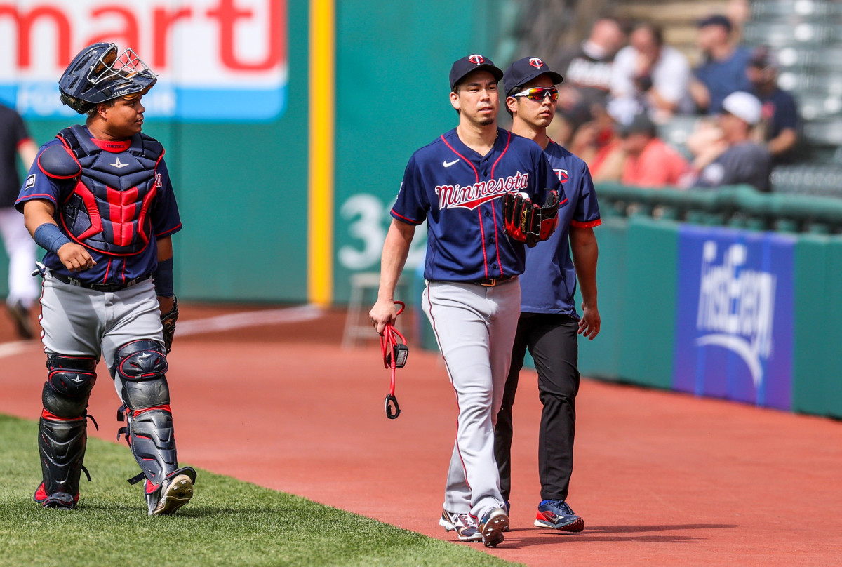 Twins righthander Kenta Maeda (center) walks catcher Willians Astudillo (left) and his interpreter Daichi Sekizaki.