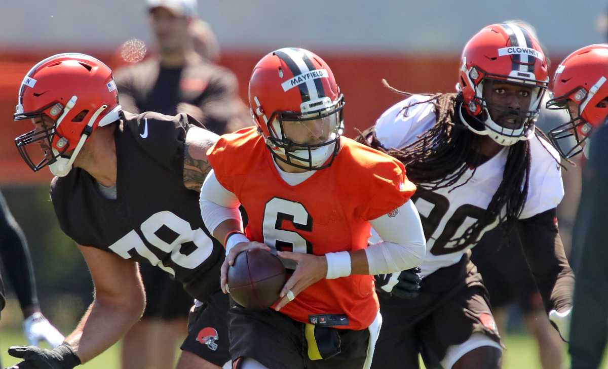 Cleveland Browns quarterback Baker Mayfield (6) looks to make a hand off to a running back under pressure from defensive end Jadeveon Clowney during an NFL football practice at the team's training facility, Wednesday, June 16, 2021, in Berea, Ohio.