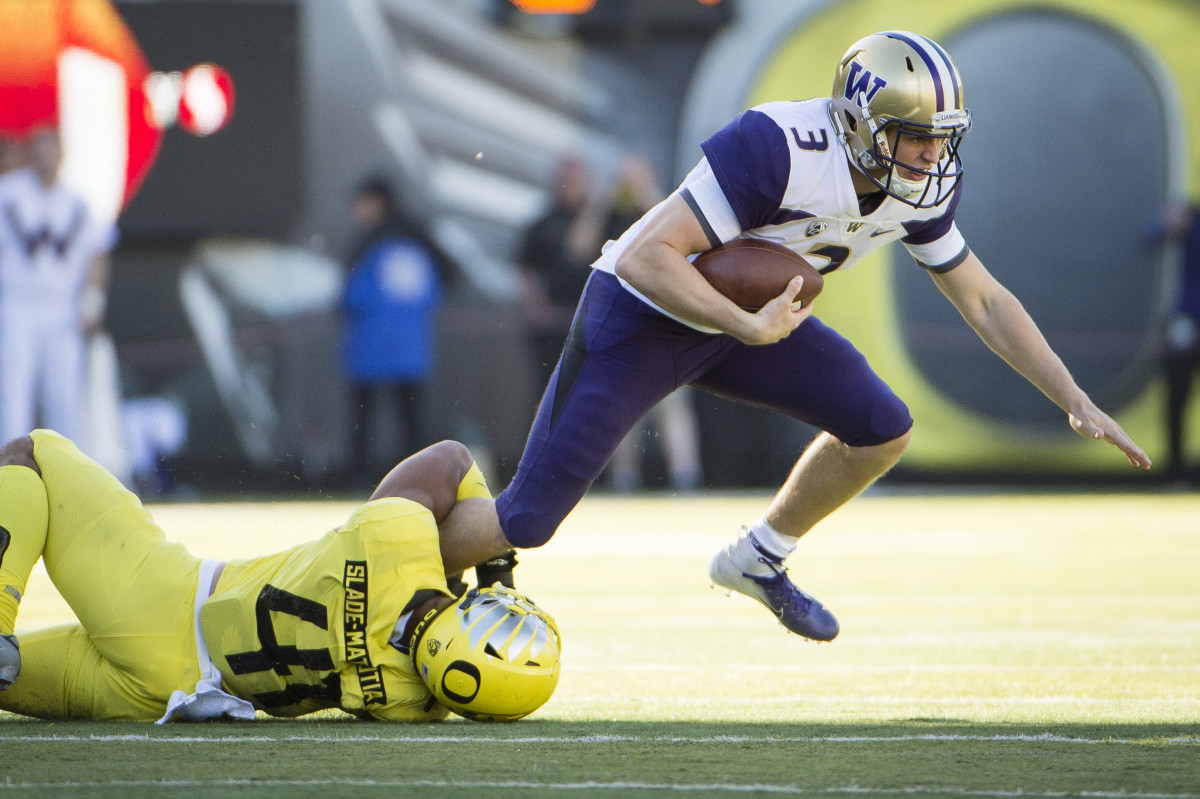Isaac Slade-Matautia (41) clutches onto Washington quarterback Jake Browning's (3) leg for a tackle for loss.