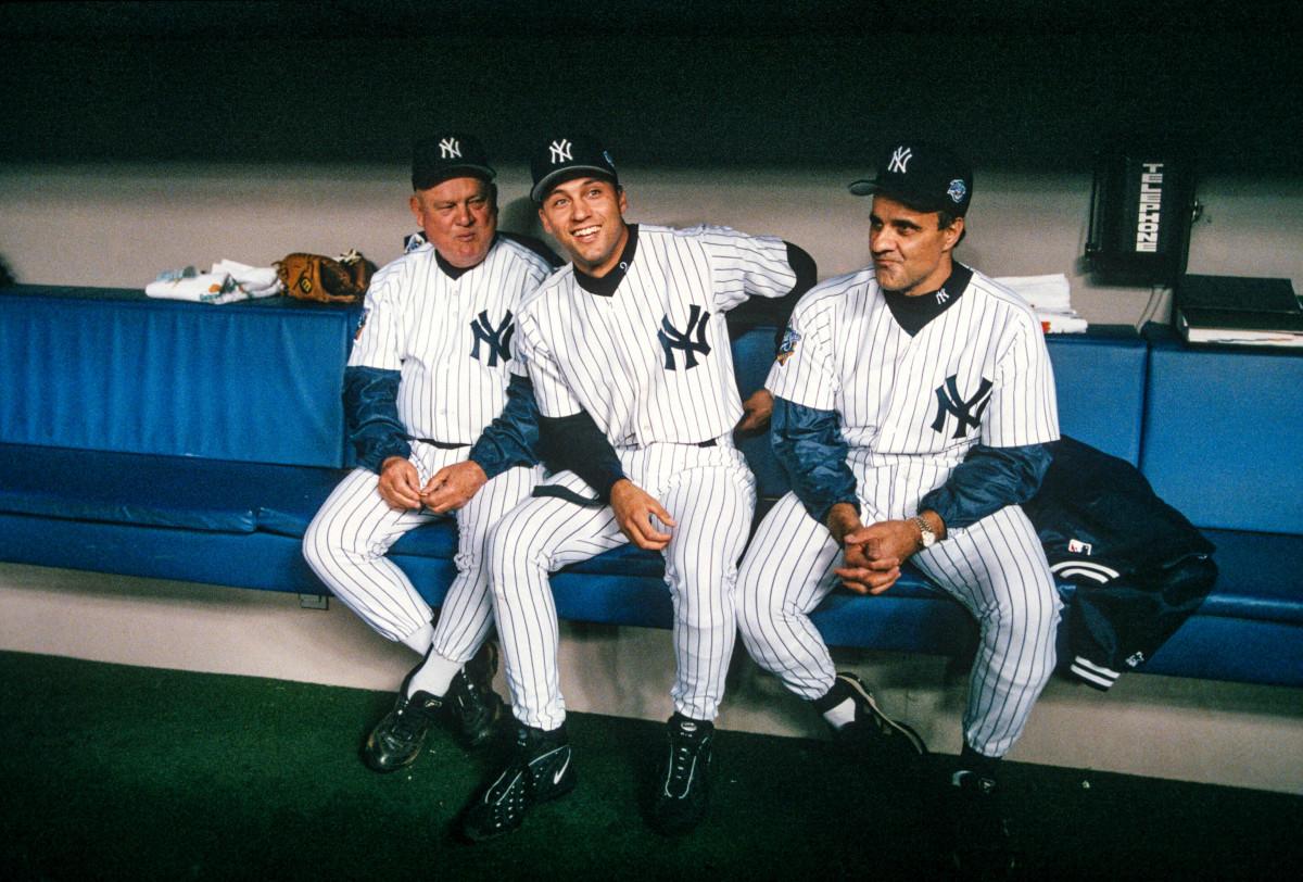 Derek Jeter sitting between Yankees bench coach Don Zimmer (left) and manager Joe Torre (right).