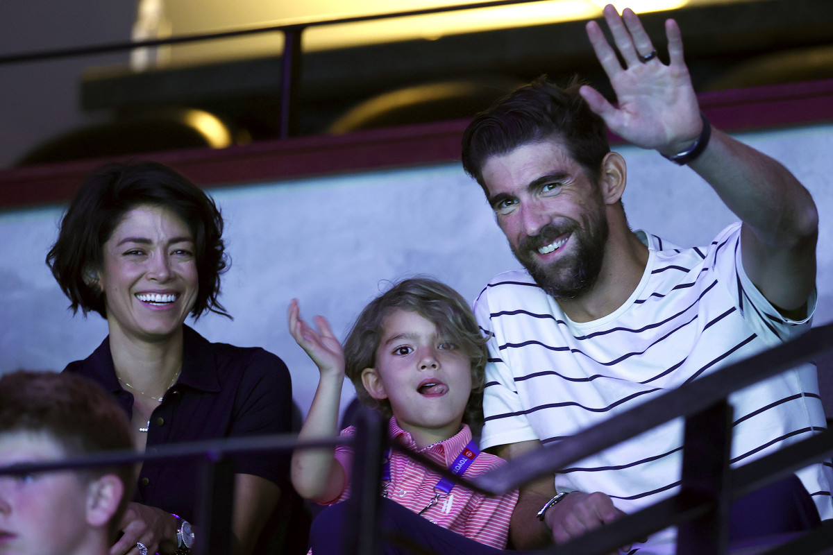 Michael Phelps and his son Boomer, with wife Nicole, wave to the crowd from the stands at the 2021 U.S. Olympic trials in Omaha.