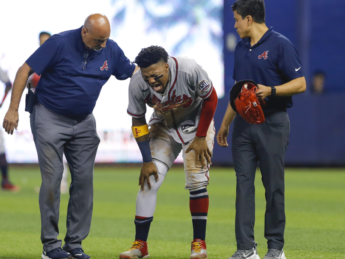 Atlanta Braves right fielder Ronald Acuna Jr. (13) reacts as he gets check on by training staff after an apparent leg injury during the fifth inning against the Miami Marlins at loanDepot Park.