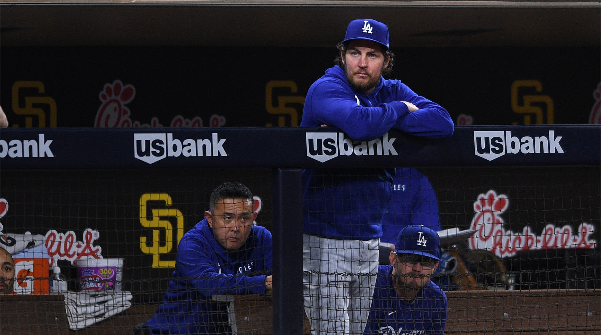 Jun 22, 2021; San Diego, California, USA; Los Angeles Dodgers starting pitcher Trevor Bauer (top) looks on from the dugout during the fifth inning against the San Diego Padres at Petco Park.