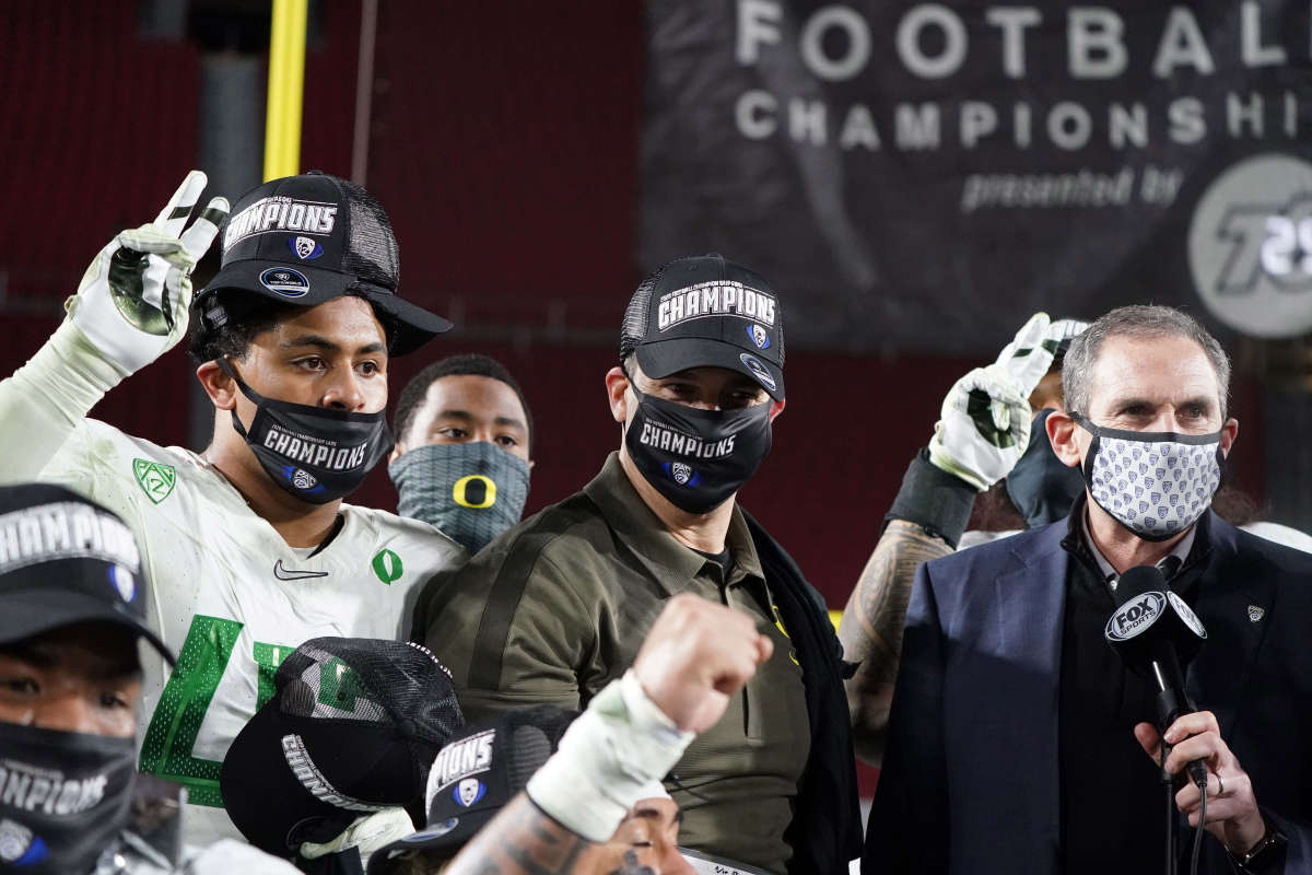 Mario Cristobal stands next to former Pac-12 commissioner Larry Scott after winning the 2020 conference title in Los Angeles.