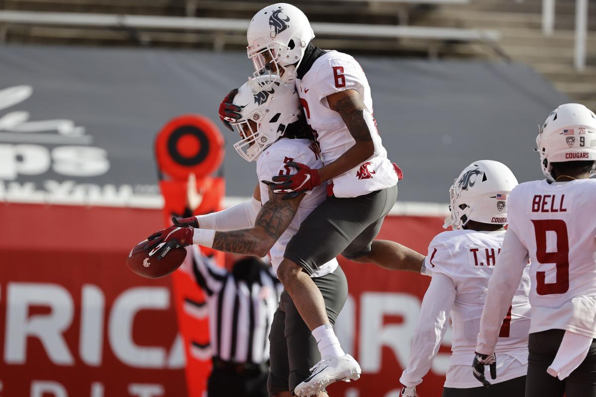 Deon McIntosh (3) celebrates a touchdown with wide receiver Jamire Calvin (6).