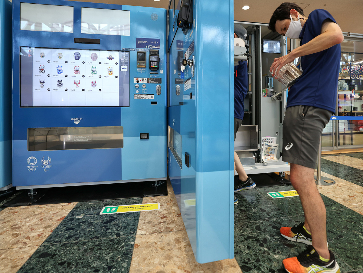 A customer buys an item from a vending machine at the Tokyo Olympics.
