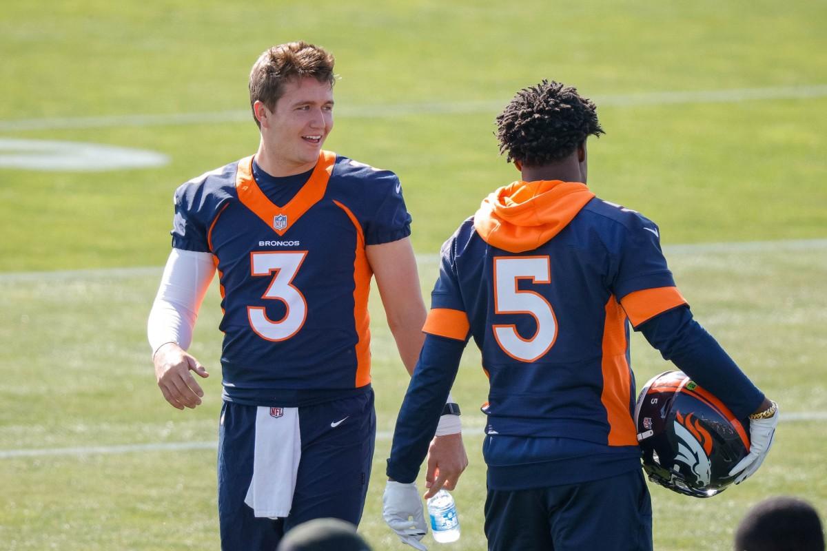 Denver Broncos quarterback Drew Lock (3) talks with quarterback Teddy Bridgewater (5) during training camp at UCHealth Training Complex.