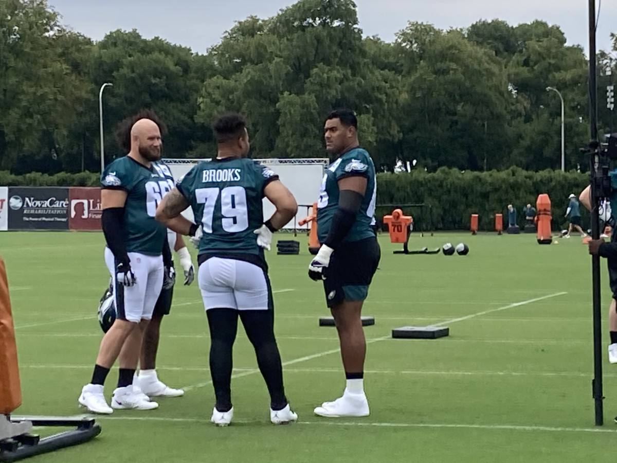 Jordan Mailata (right) talks to teammates Lane Johnson (left) and Brandon Brooks prior to Thursday's practice on July 29, 2021