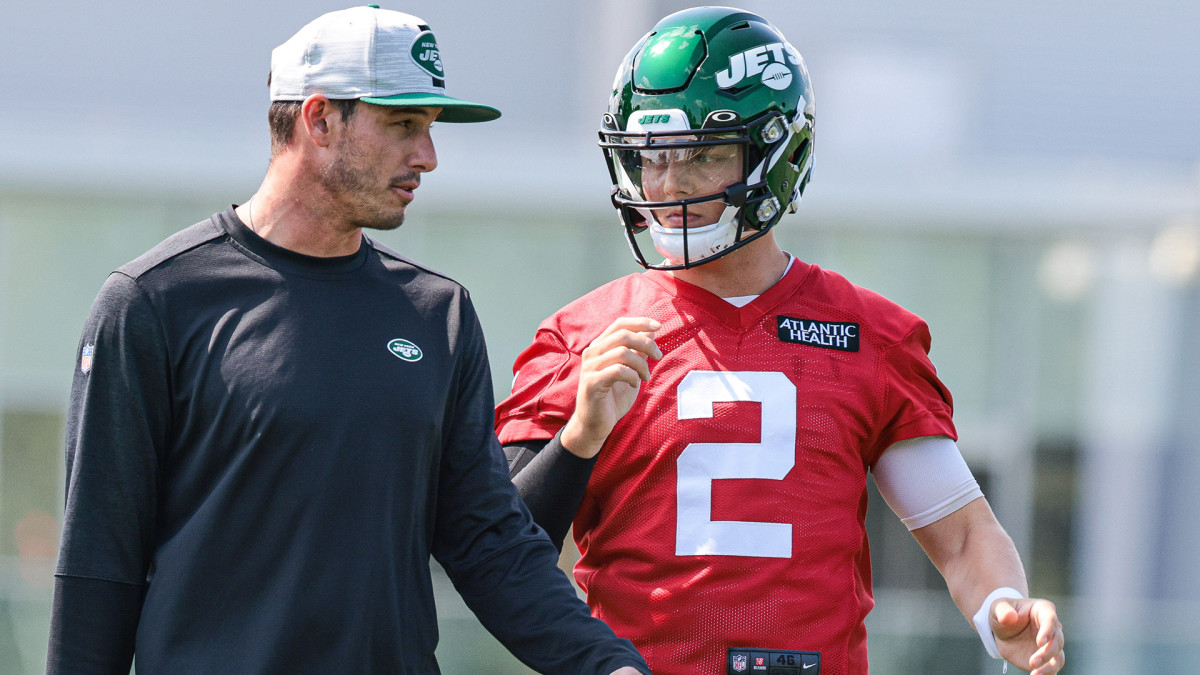 Zach Wilson talks with quarterbacks coach Rob Calabrese during his first practice with the Jets