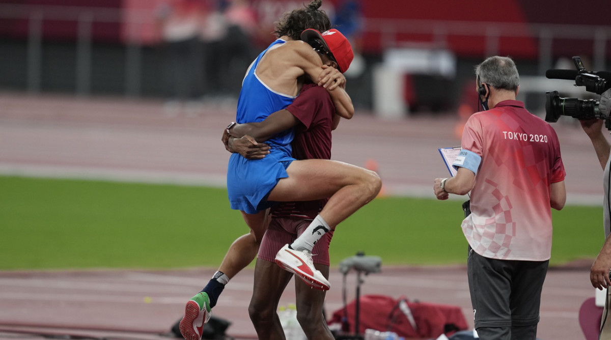 Gianmarco Tamberi (ITA) reacts after sharing gold with Mutaz Essa Barshim (QAT), center, in the men's high jump during the Tokyo 2020 Olympic Summer Games at Olympic Stadium.