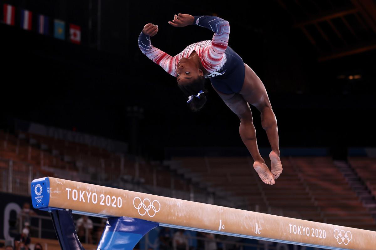 Simone Biles doing a backflip on balance beam
