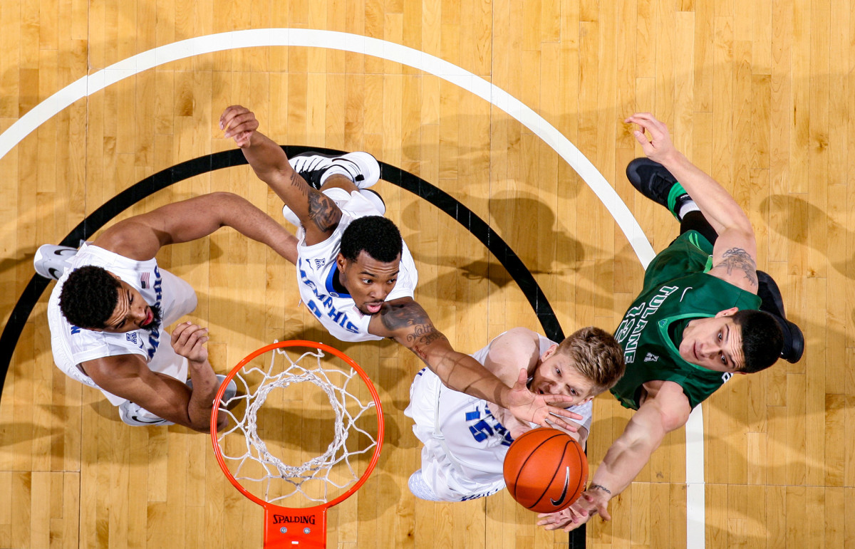 NFL player Sammis Reyes goes up for a rebound while playing for Tulane University's basketball team
