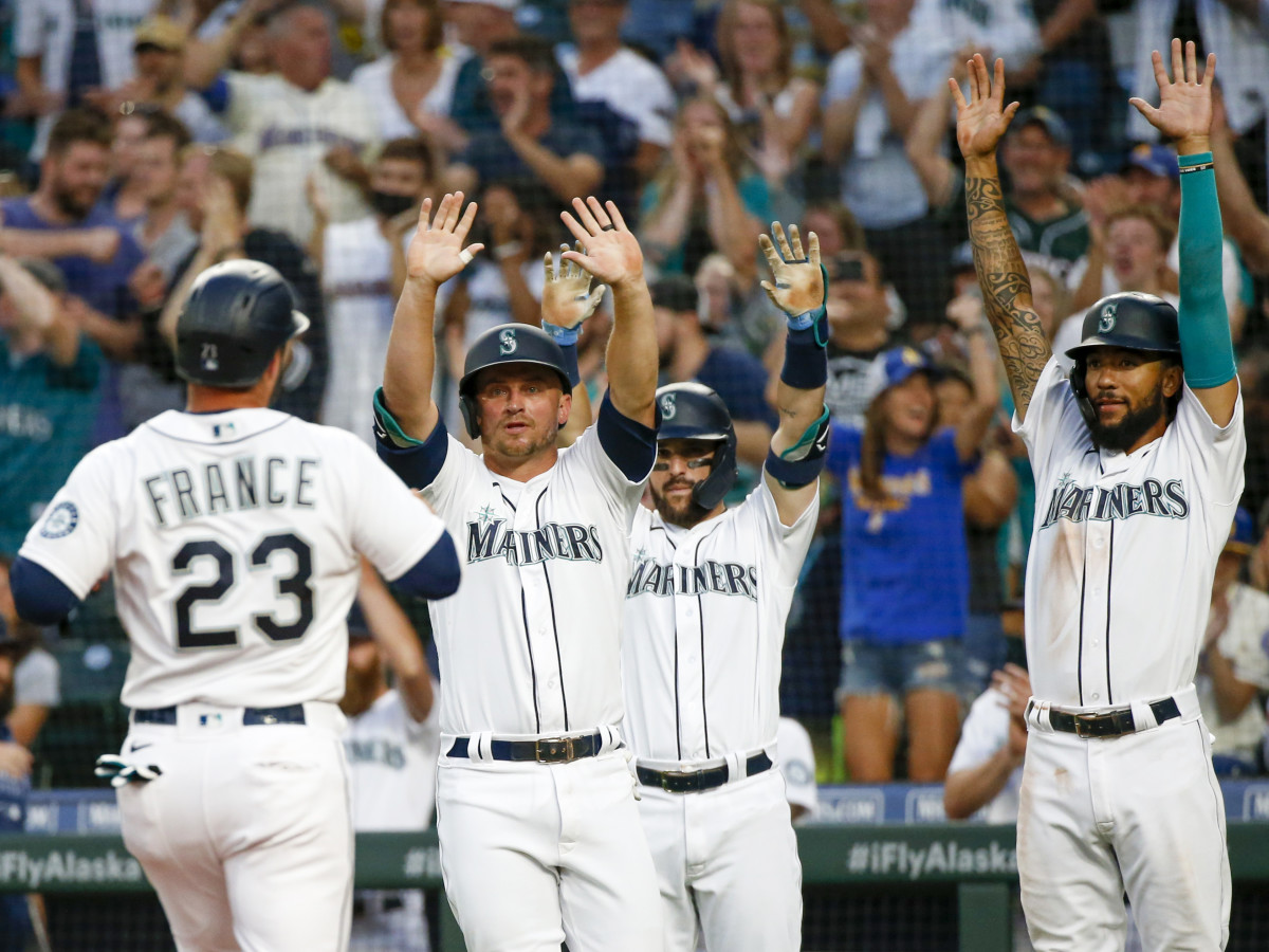 Jul 26, 2021; Seattle, Washington, USA; Seattle Mariners third baseman Kyle Seager (15, left), first baseman Luis Torrens (22) and shortstop J.P. Crawford (3, right) greet designated hitter Ty France (23) as he scores a run against the Houston Astros during the fourth inning at T-Mobile Park. Seager and Crawford also scored runs on the play.