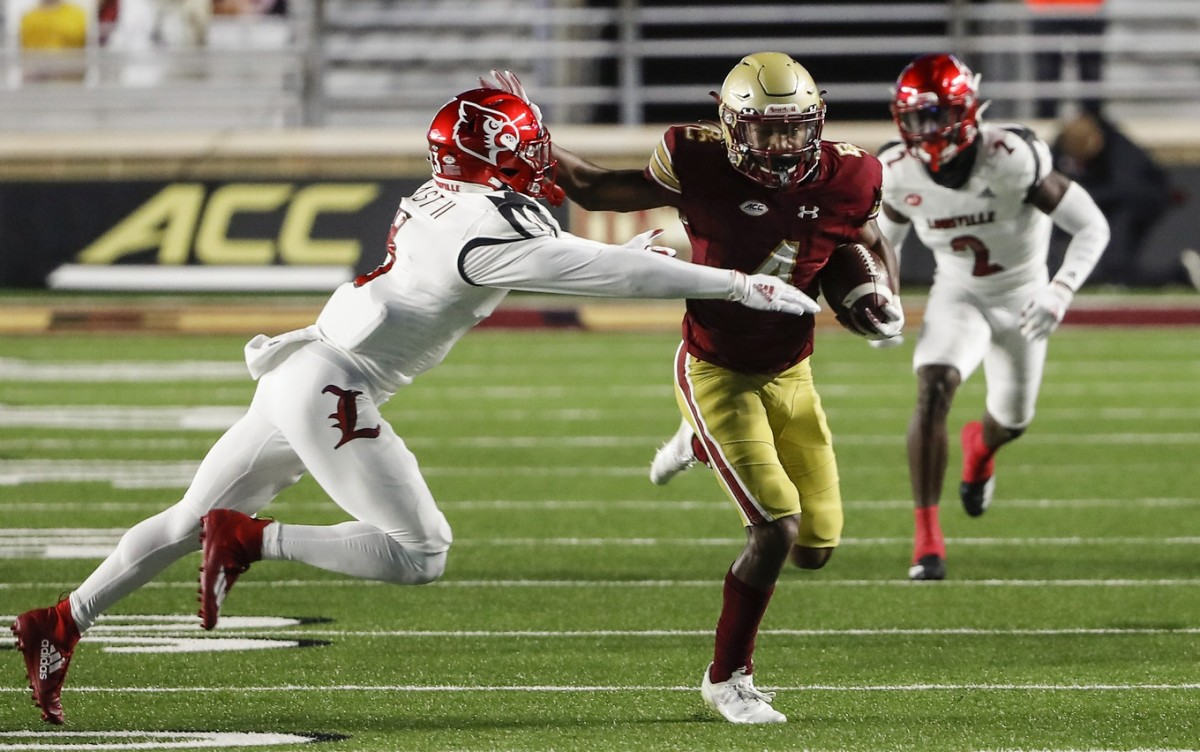 Nov 28, 2020; Chestnut Hill, Massachusetts, USA; Boston College Eagles wide receiver Zay Flowers (4) stiff arms Louisville Cardinals defensive back Russ Yeast (3) during the first half at Alumni Stadium.