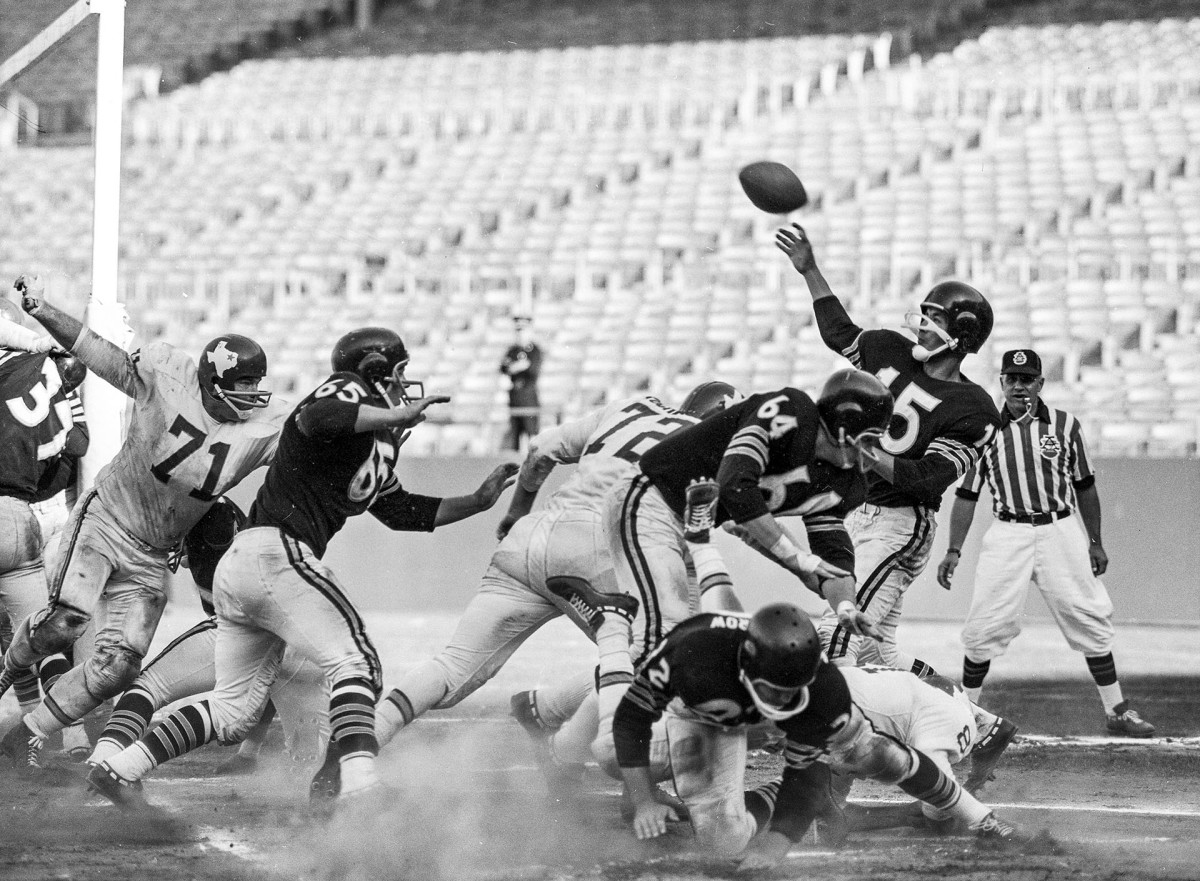 Raiders quarterback Tom Flores throws a pass as he's hit during a 1961 game against the Dallas Texans