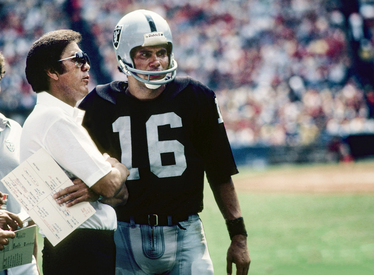 Tom Flores and Jim Plunkett talk on the sideline during a game in 1982