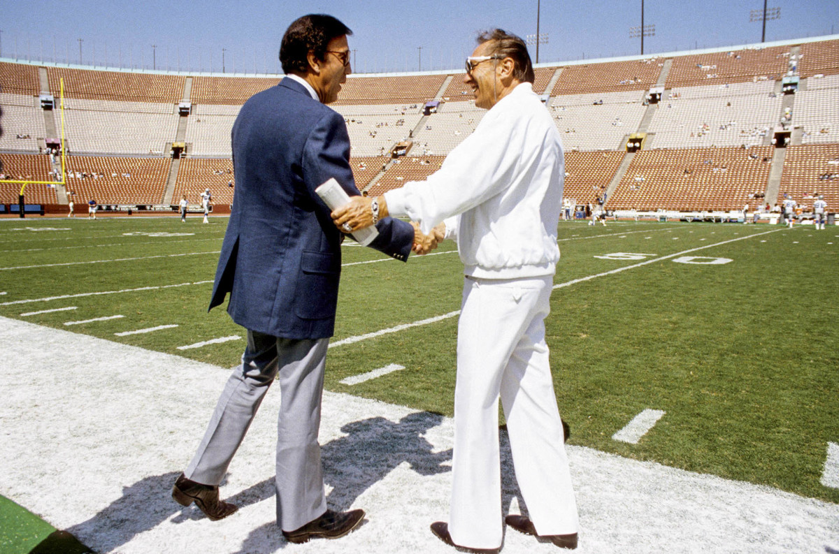 Tom Flores, then with the Seattle Seahawks, greets Raiders owner Al Davis before a game