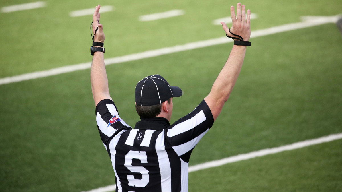 A college football ref signals for a touchdown
