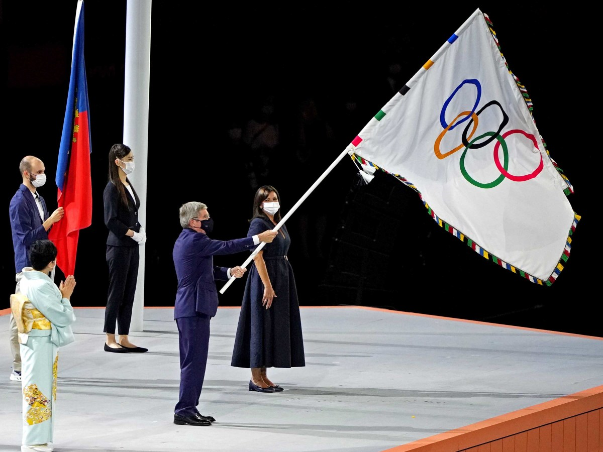 IOC president Thomas Bach waves the Olympic flag during the closing ceremony for the Tokyo 2020 Olympic Summer Games at Olympic Stadium.