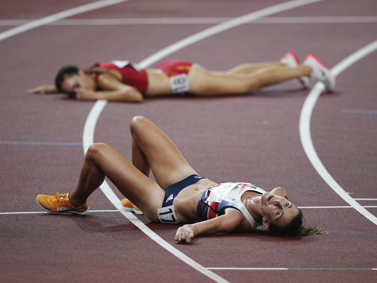 Jessica Judd (GBR), front, and Lucia Rodriguez (ESP) lay on the track after the women's 5000m preliminary, round one, heat one during the Tokyo 2020 Olympic Summer Games at Olympic Stadium.