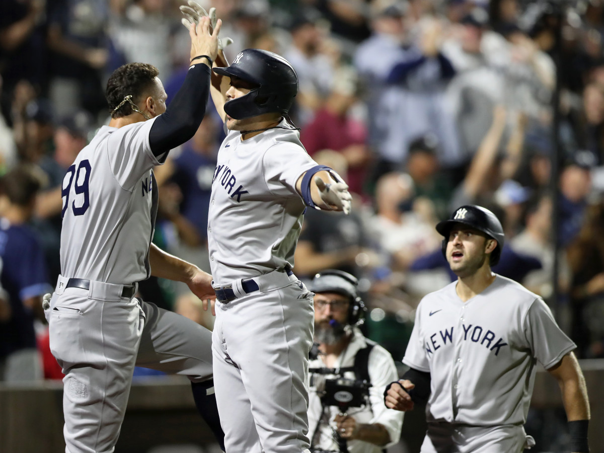 Aug 12, 2021; Dyersville, Iowa, USA; New York Yankees designated hitter Giancarlo Stanton (middle) celebrates with right fielder Aaron Judge (99) after hitting a home run against the Chicago White Sox during the ninth inning at the Field of Dreams.