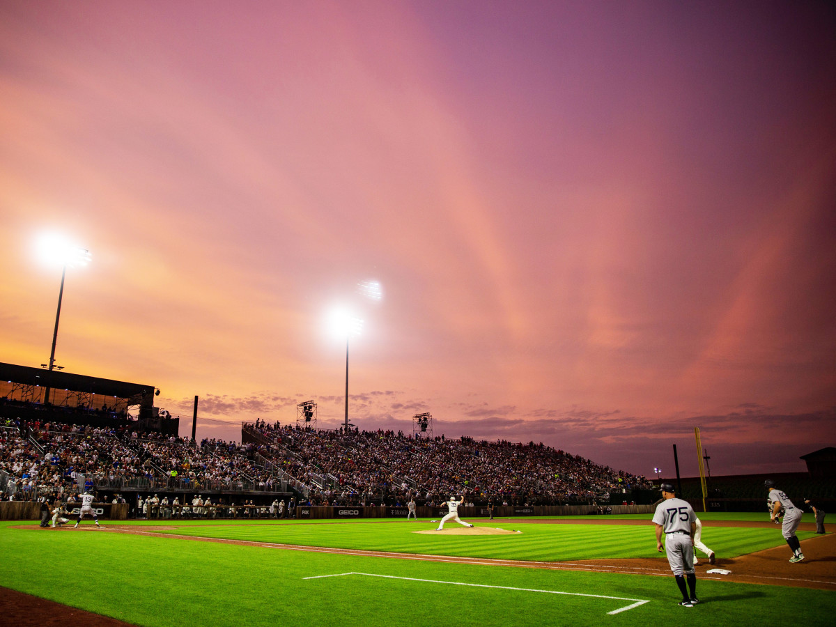 Orange hues paint the sky during the game between the New York Yankees and the Chicago White Sox near the Field of Dreams movie site outside of Dyersville, Thursday, Aug. 12, 2021.