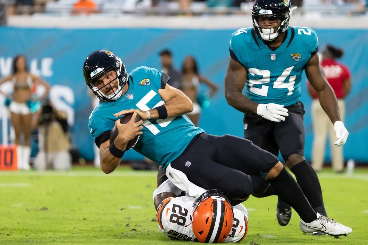 Aug 14, 2021; Jacksonville, Florida, USA; Jacksonville Jaguars quarterback Gardner Minshew (15) is sacked by Cleveland Browns linebacker Jeremiah Owusu-Koramoah (28) during the second quarter at TIAA Bank Field. Mandatory Credit: Matt Pendleton-USA TODAY Sports