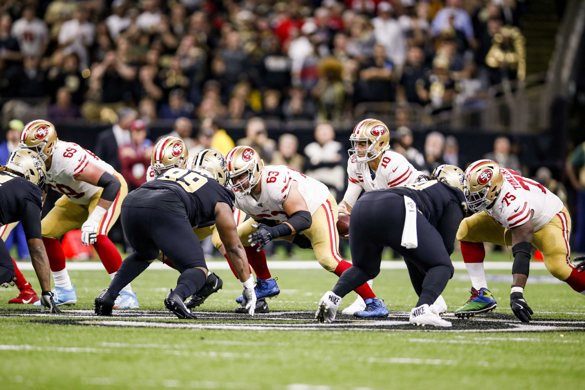 The 49ers' offensive line at the snap in a game against the Saints