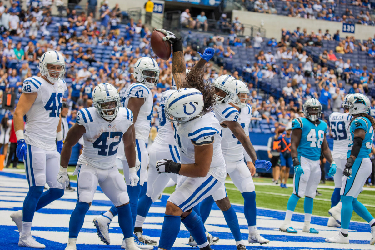 Aug 15, 2021; Indianapolis, Indiana, USA; Indianapolis Colts running back Benny LeMay (42) celebrates his touchdown with offensive tackle Sam Tevi (71) spiking the ball in the second half against the Carolina Panthers at Lucas Oil Stadium.