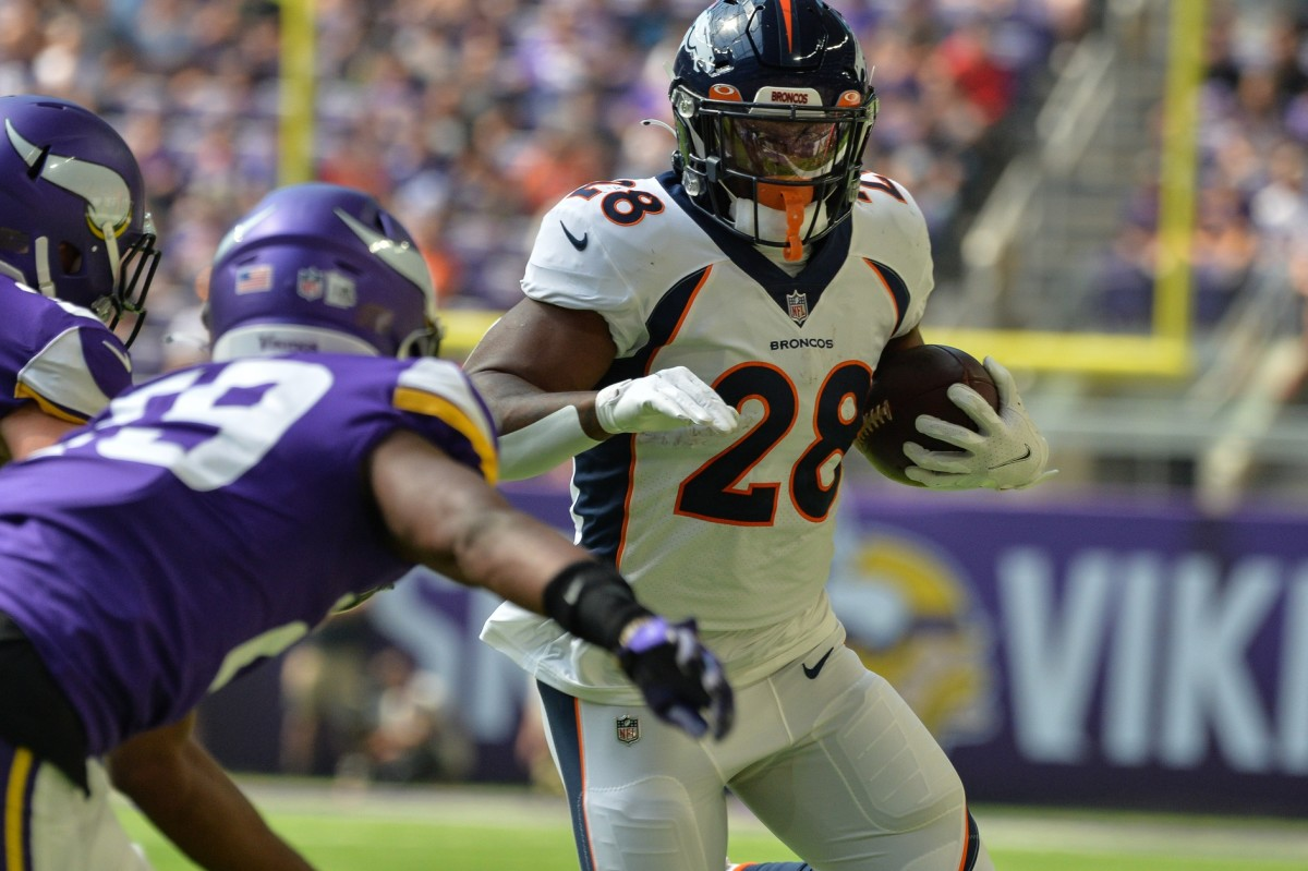 Denver Broncos running back Royce Freeman (28) runs the ball as Minnesota Vikings defensive back Kris Boyd (29) moves in for the tackle during the first quarter at U.S. Bank Stadium.