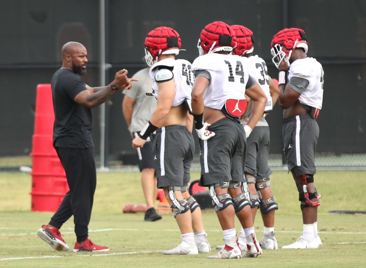 Jamar Cain coaching the OU defensive ends and outside linebackers, including Reggie Grimes (14)