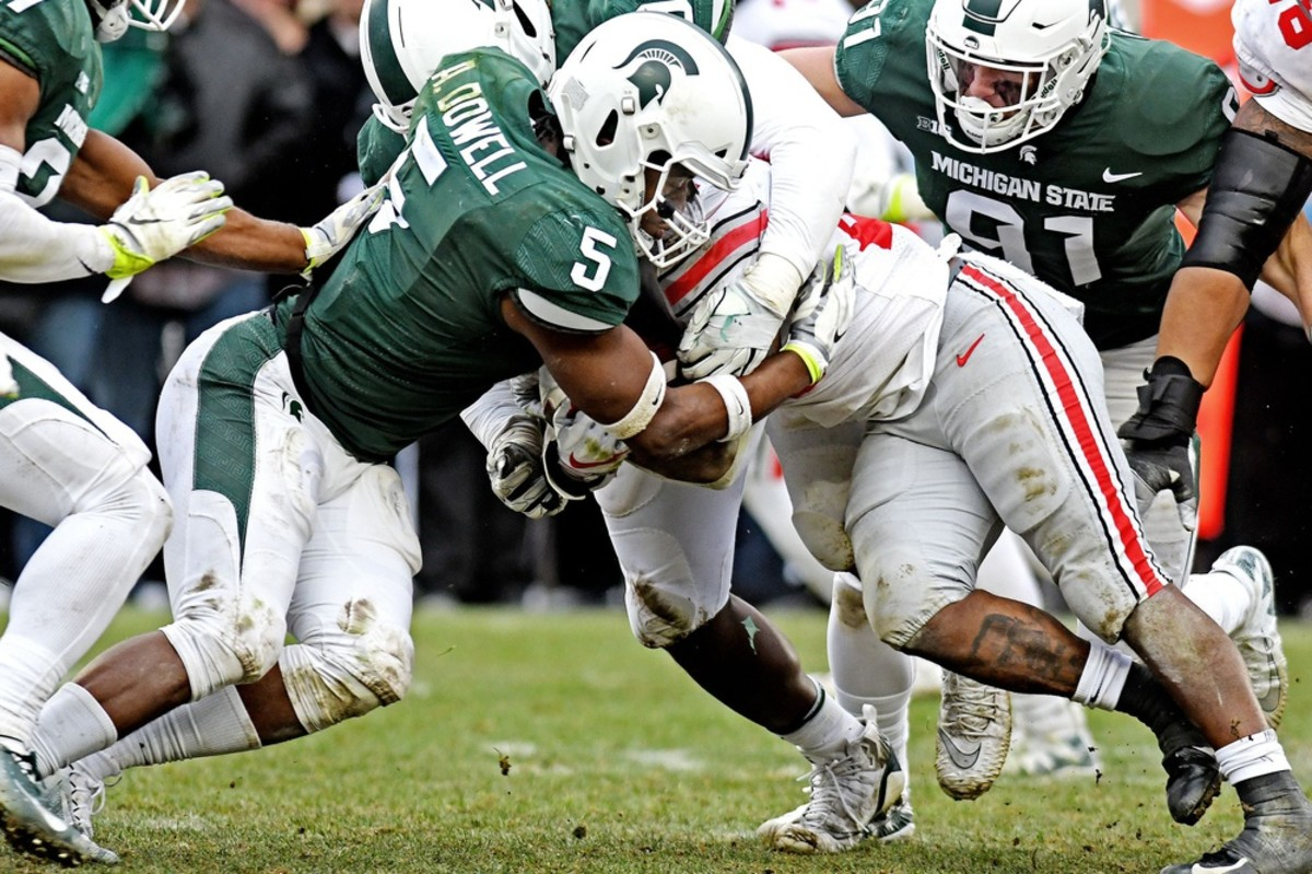 Michigan State's Andrew Dowell, left, tackles Ohio State's Mike Weber Jr.© Nick King/Lansing State Journal