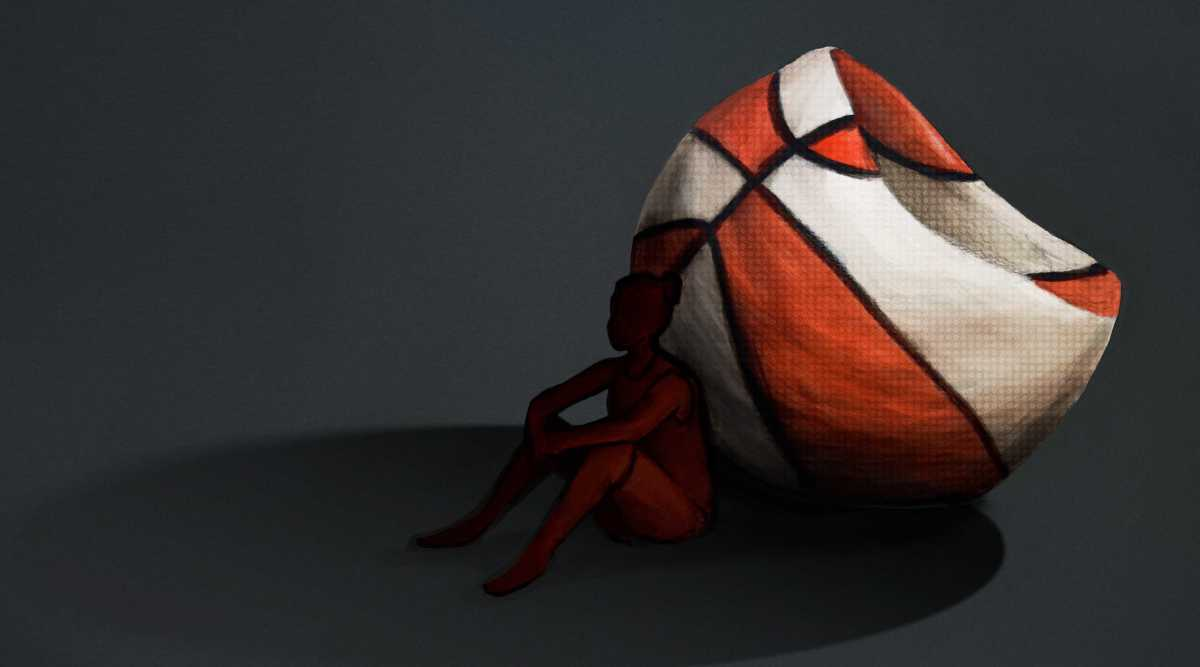 A silhouette of a female basketball player leaning up against a deflated orange and white basketball