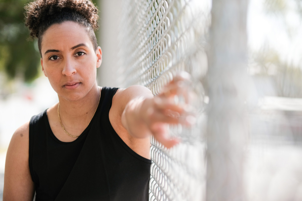 Layshia Clarendon with her arm pressed against a fence