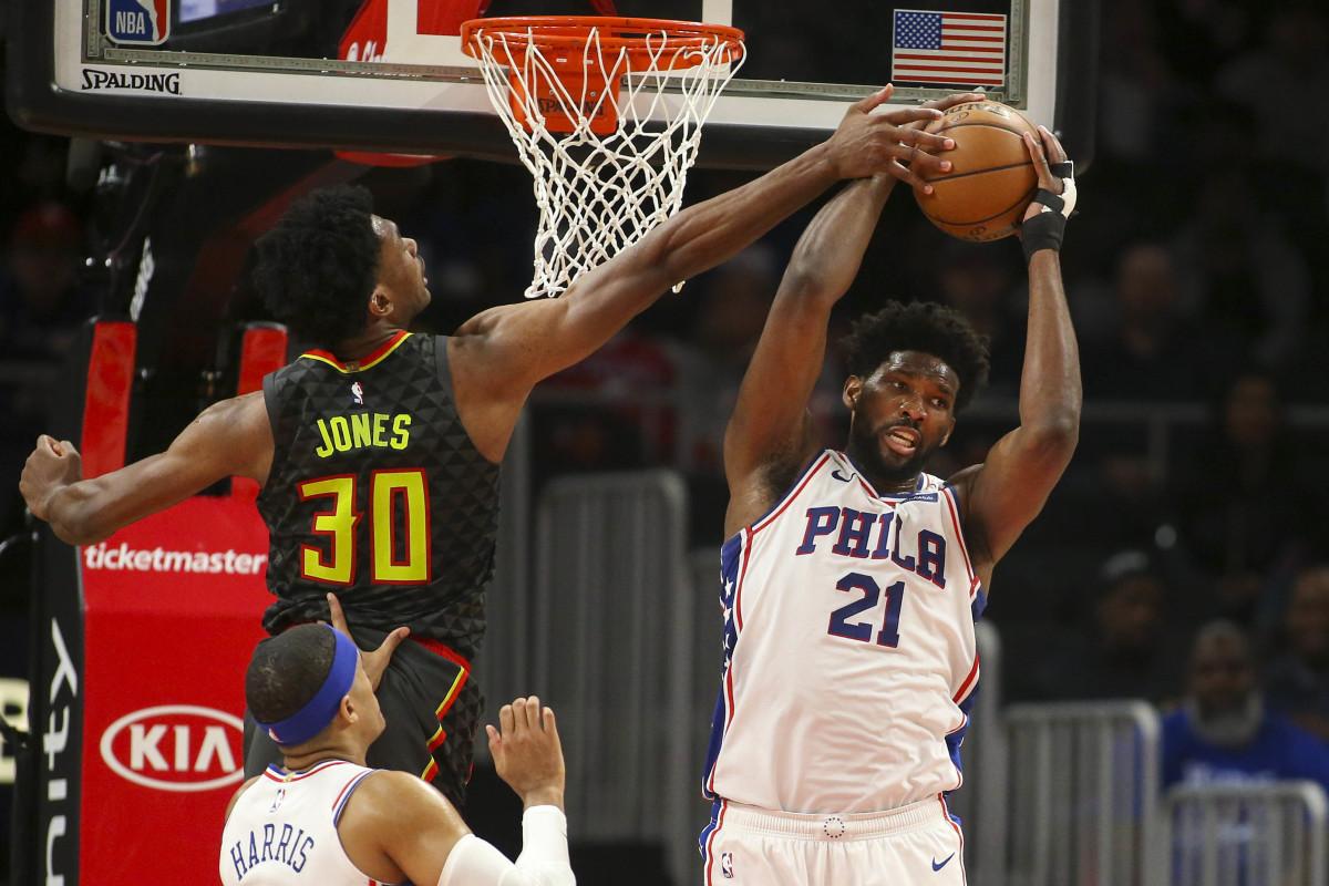 Philadelphia 76ers center Joel Embiid grabs a rebound past Atlanta Hawks center Damian Jones