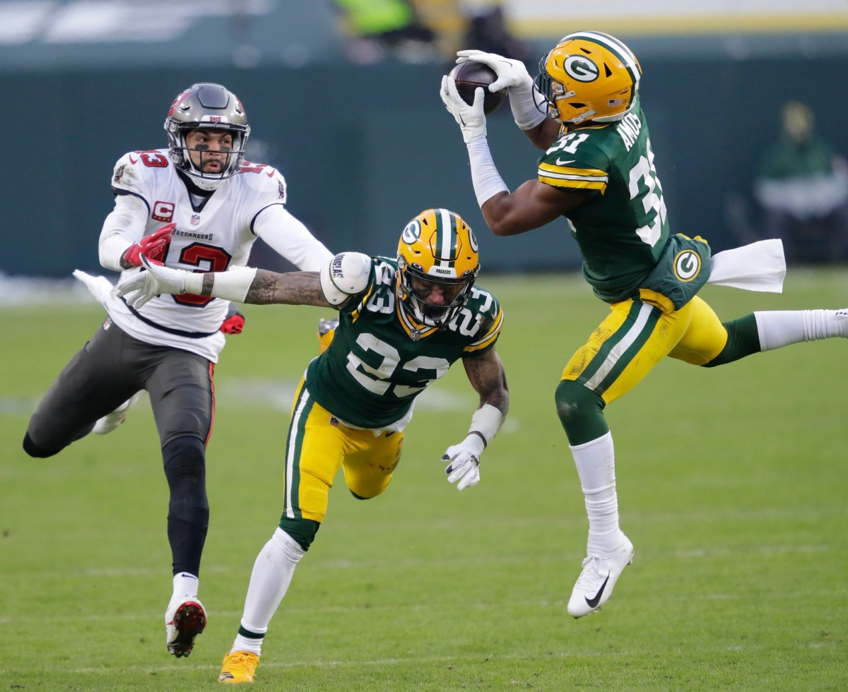Green Bay Packers safety Adrian Amos (31) intercepts a pass intended for Buccaneers receiver Mike Evans (13) as cornerback Jaire Alexander (23) helps on the play.© Dan Powers/USA TODAY NETWORK-Wisconsin via Imagn Content Services, LLC