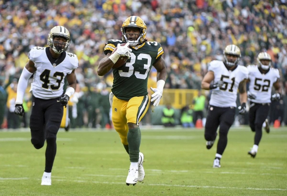 Green Bay Packers running back Aaron Jones (33) runs past the New Orleans Saints for a touchdown. Mandatory Credit: Benny Sieu-USA TODAY