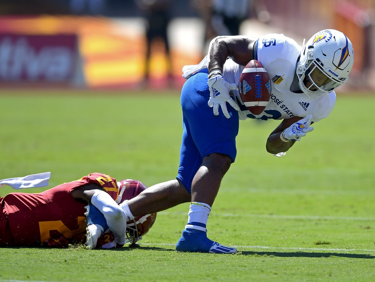 Sep 4, 2021; Los Angeles, California, USA;  San Jose State Spartans running back Tyler Nevens (23) hangs on to the ball for a first down before he is stopped by USC Trojans safety Calen Bullock (27)in the first half of the game at United Airlines Field at Los Angeles Memorial Coliseum. Mandatory Credit: Jayne Kamin-Oncea-USA TODAY Sports