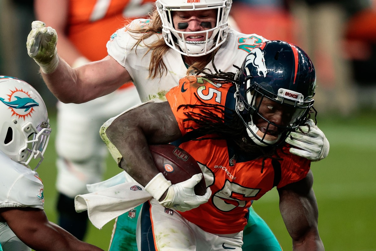 Nov 22, 2020; Denver, Colorado, USA; Denver Broncos running back Melvin Gordon III (25) is pulled down by Miami Dolphins linebacker Andrew Van Ginkel (43) in the fourth quarter at Empower Field at Mile High. Mandatory Credit: Isaiah J. Downing-USA TODAY Sports