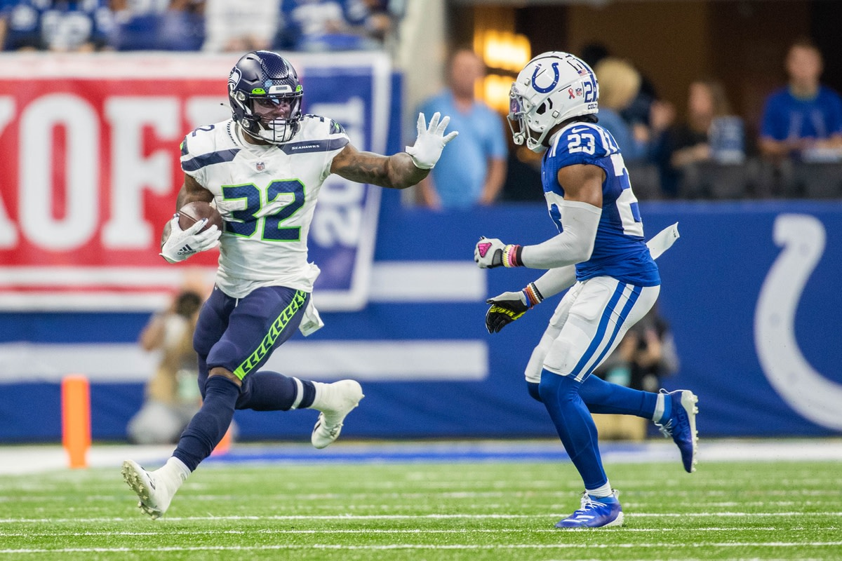 Sep 12, 2021; Indianapolis, Indiana, USA; Seattle Seahawks running back Chris Carson (32) runs the ball while Indianapolis Colts cornerback Kenny Moore II (23) defends in the second quarter at Lucas Oil Stadium. Mandatory Credit: Trevor Ruszkowski-USA TODAY Sports