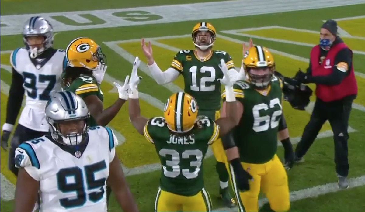 Aaron Rodgers, Davante Adams and Aaron Jones look up, hands raised, as they celebrate a touchdown against the Panthers during a 2020 game