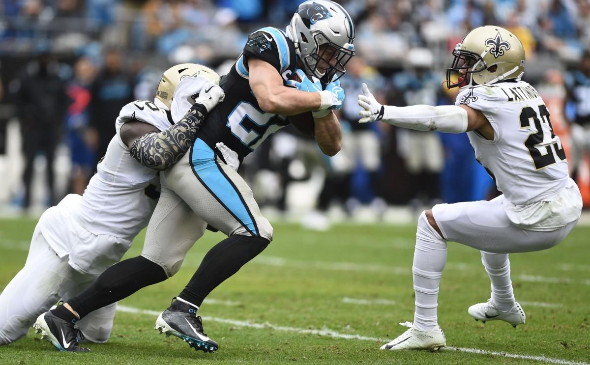 Carolina Panthers running back Christian McCaffrey (22) is tackled by New Orleans Saints linebacker Demario Davis (56) and cornerback Marshon Lattimore (23). Mandatory Credit: Bob Donnan-USA TODAY