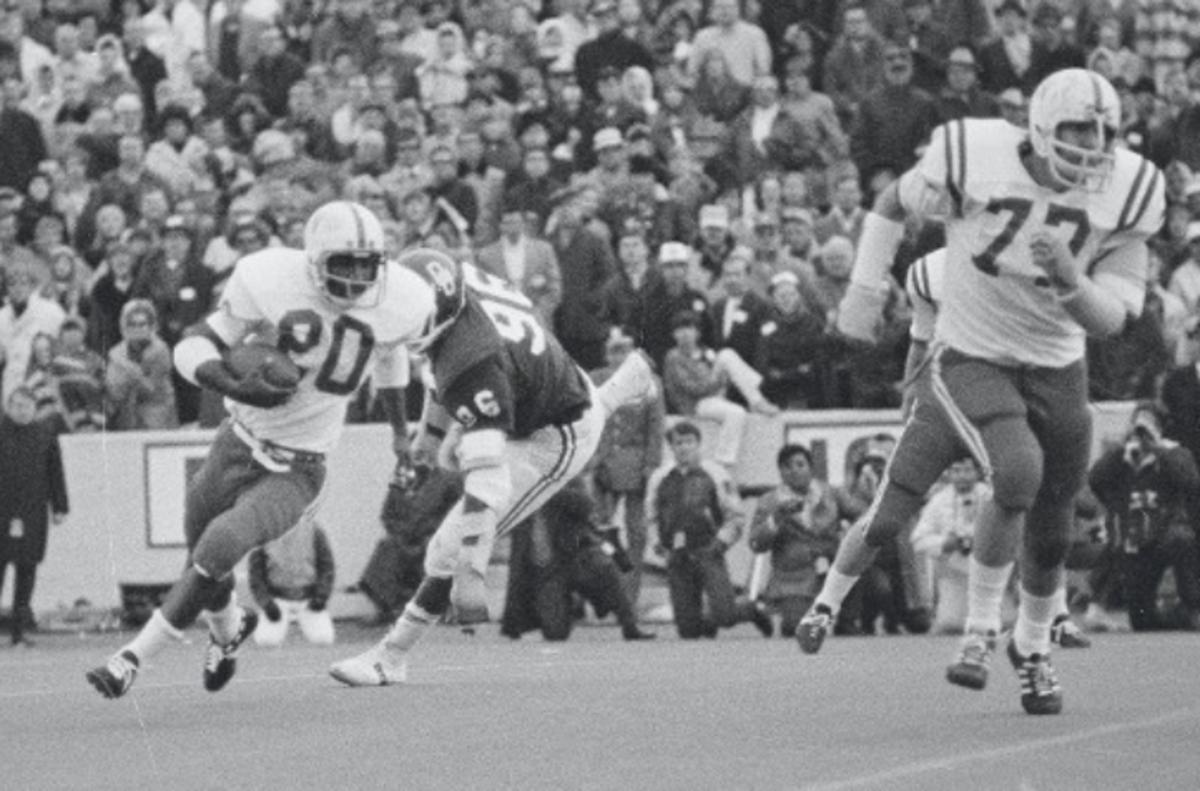 Johnny Rodgers runs away from Ray Hamilton