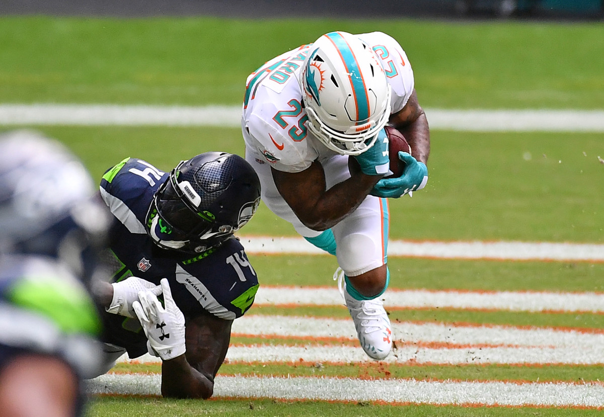 Xavien Howard goes to the ground as he secures an interception in front of Seahawks receiver DK Metcalf during a game in 2020