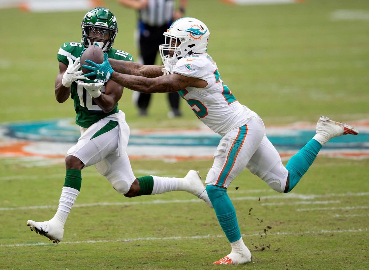 Xavien Howard reaches to grab an interception in front of Jets receiver Jeff Smith during a 2020 game